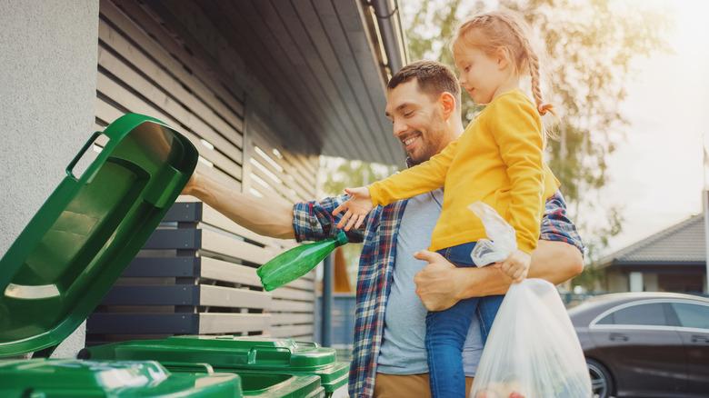 Dad and daughter throwing away garbage