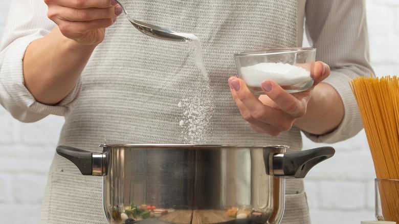 Person sprinkling salt into pasta pot