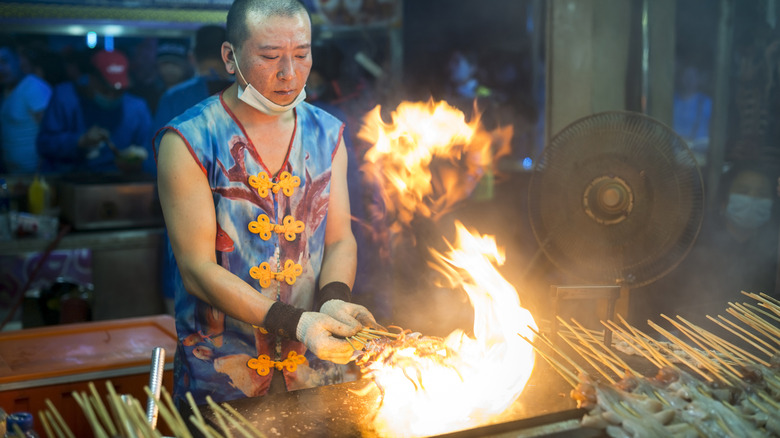 Street vendor cooks squid skewers over open flame