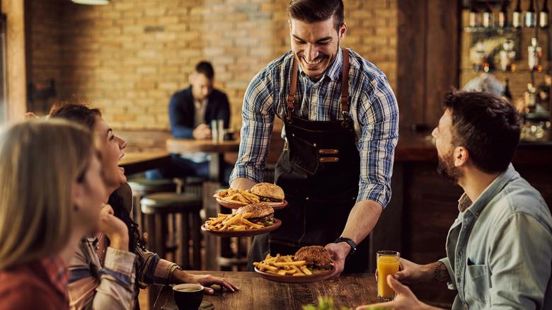 Waiter serving food in restaurant