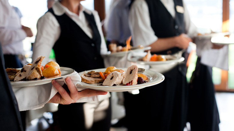 waiters carrying plates of food