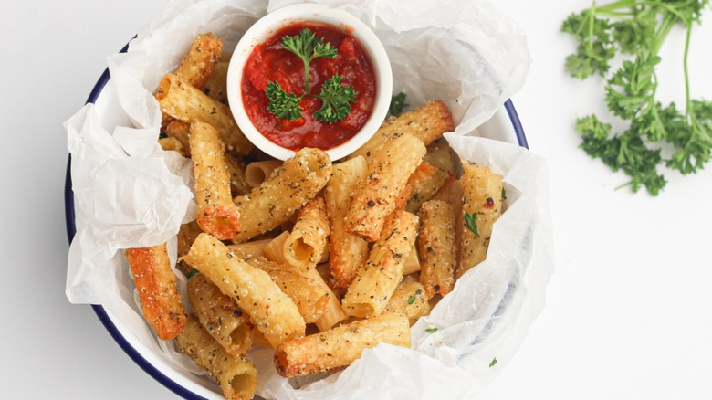 Pasta chips sitting on a platter with red sauce