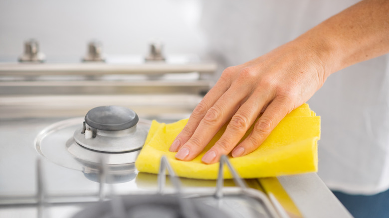 Hand cleaning stove top with sponge