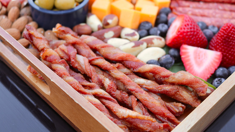 Twisted bacon on charcuterie cheese board