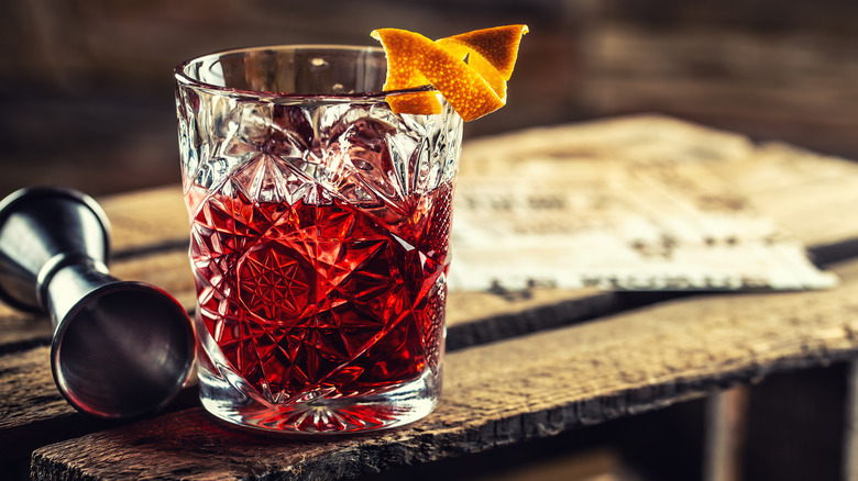 Negroni cocktail with jigger on wooden board