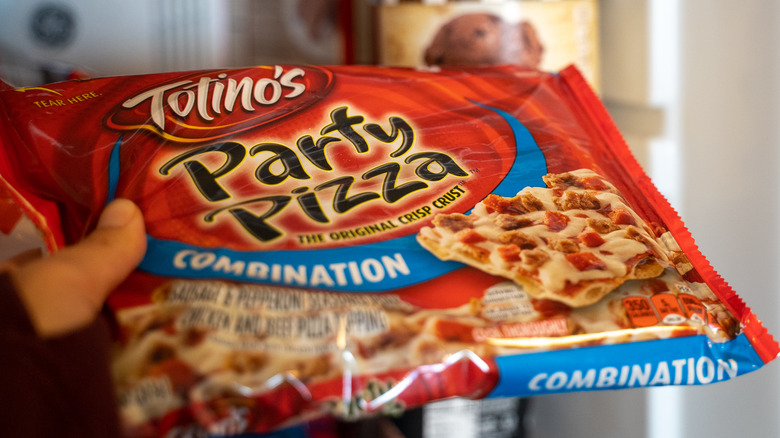 Hand holding Totino's Party Pizza packaging