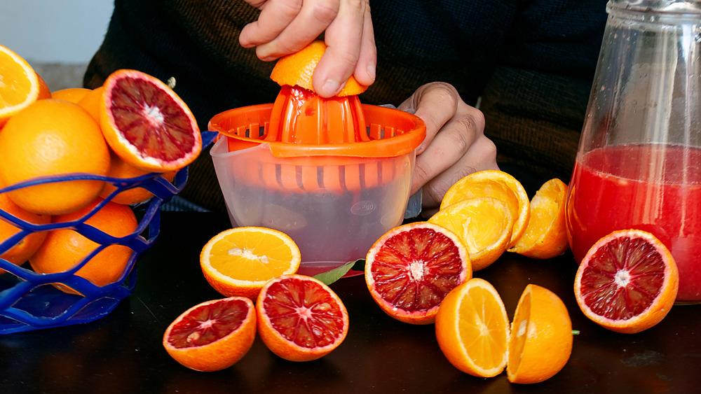 Squeezing blood oranges hand