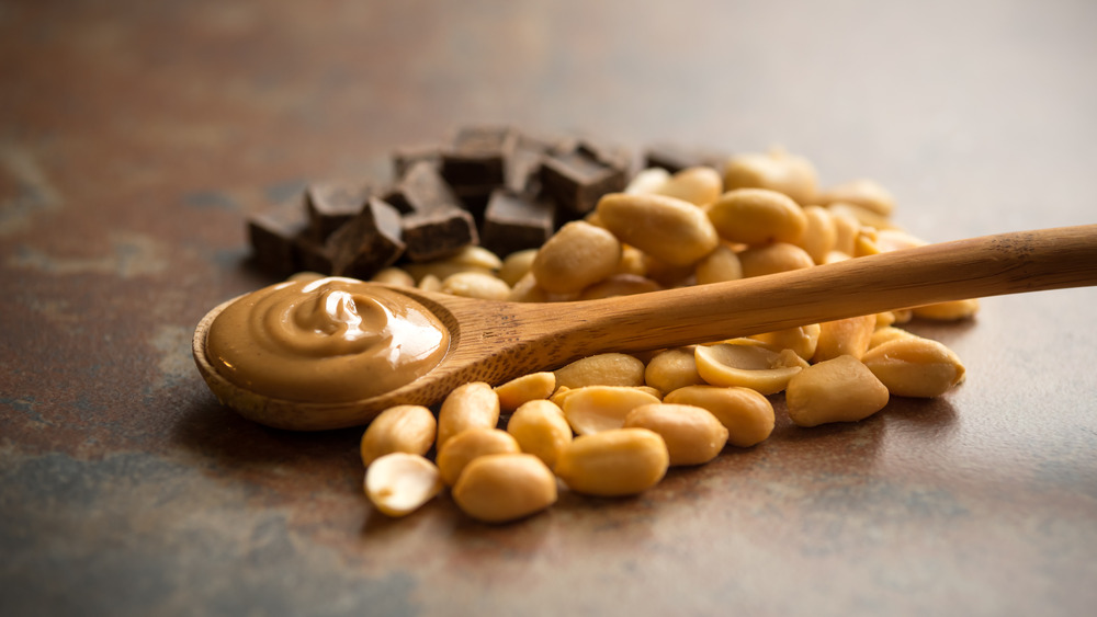 Chocolate and peanuts under wooden spoon with peanut butter