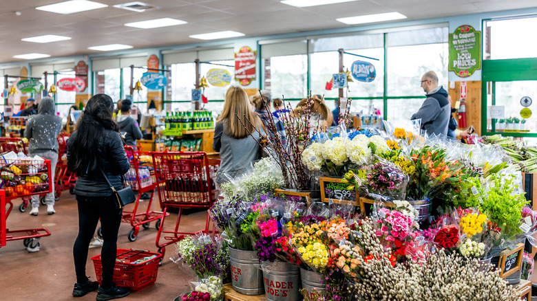 Shoppers at Trader Joe's with a flower display in the foreground