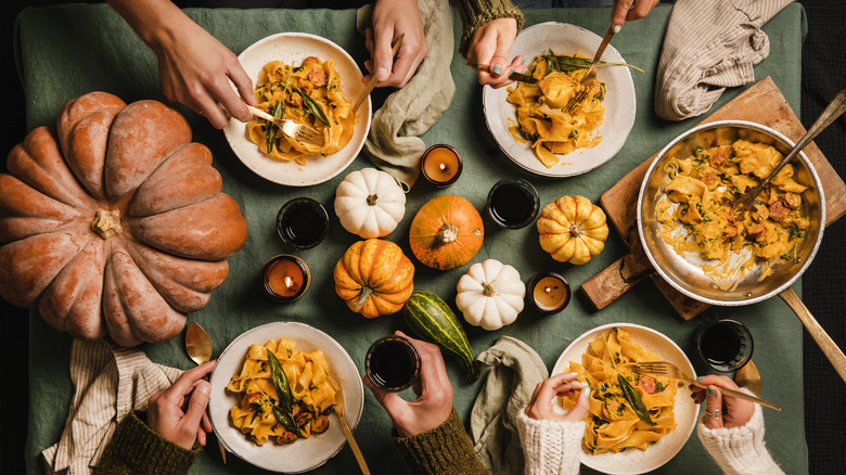 Table set with pumpkins and bowls of pasta