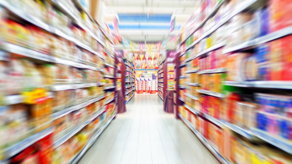 Blurred grocery store aisle full of food brands