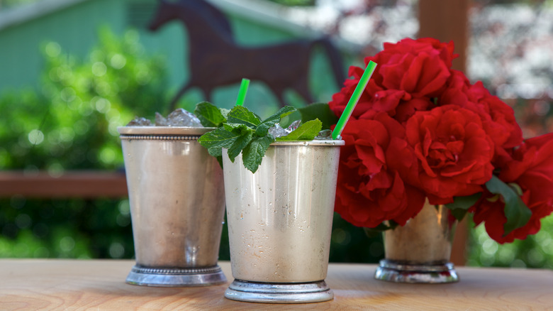 MInt-garnished drinks in silver cups in front of horse statue with roses