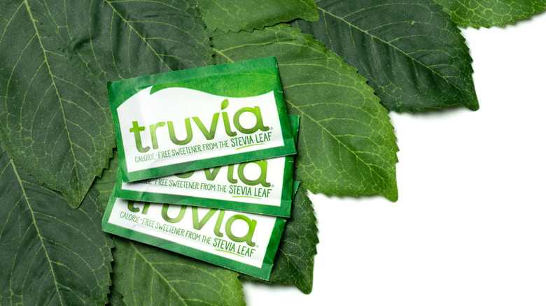 Truvia packets on top of green leaves