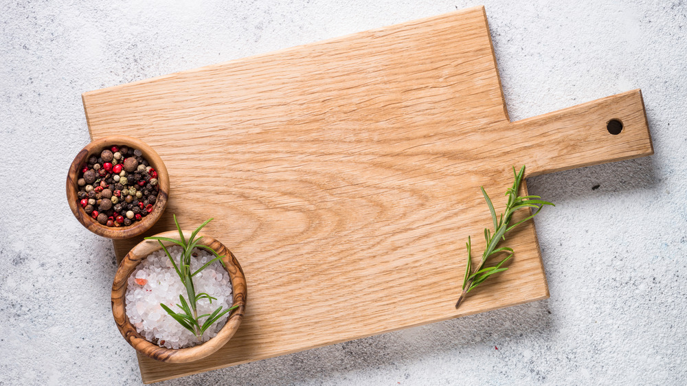 Wooden cutting board with salt, pepper, and herbs