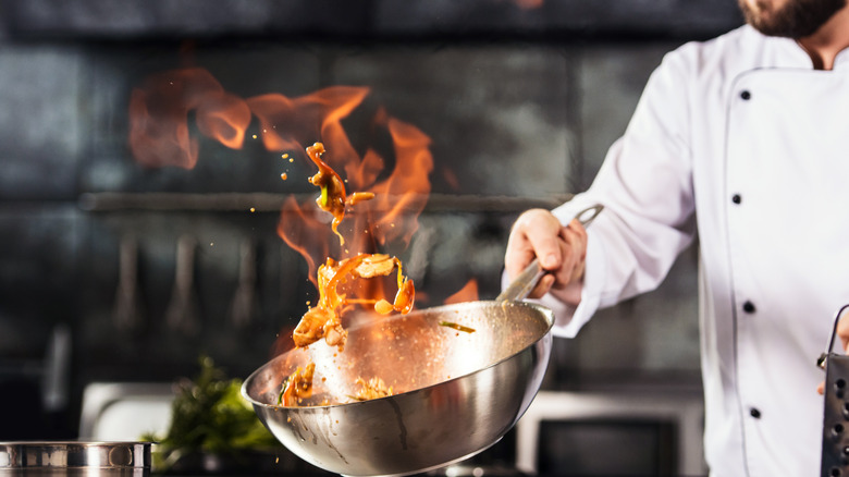 Chef in white coat holding a wok with flame