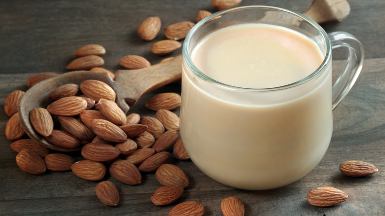 Almond milk in a cup next to almonds
