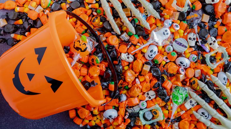 Pumpkin bucket spilling out Halloween candy