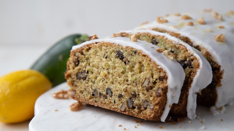 sliced loaf of zucchini walnut bread with lemon glaze on a counter by a lemon and zucchini