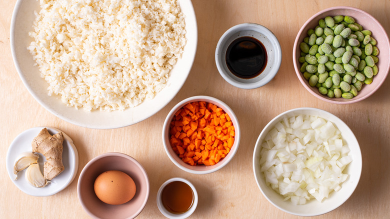 Ingredients gathered on a wooden table to make cauliflower fried rice