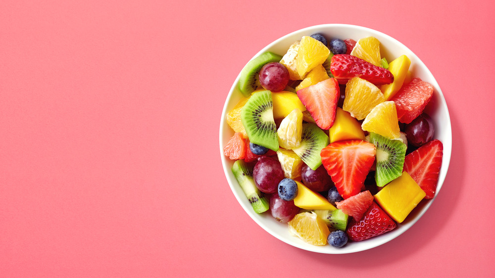 bowl of fruit with berries, kiwi, oranges and grapes