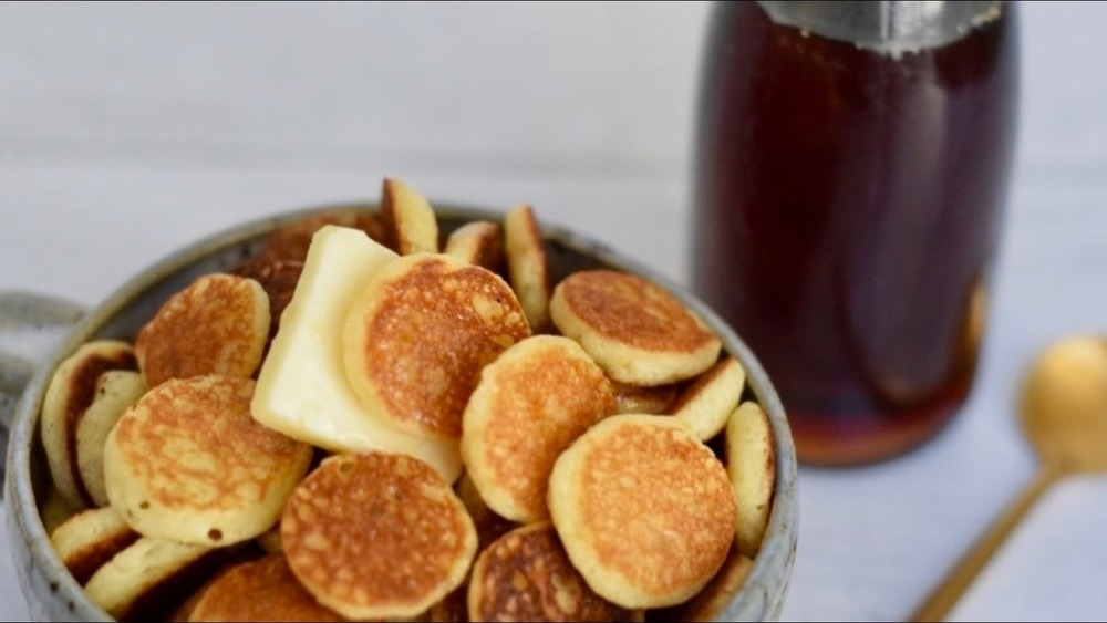 Cereal pancakes with syrup and butter in blue ceramic bowl