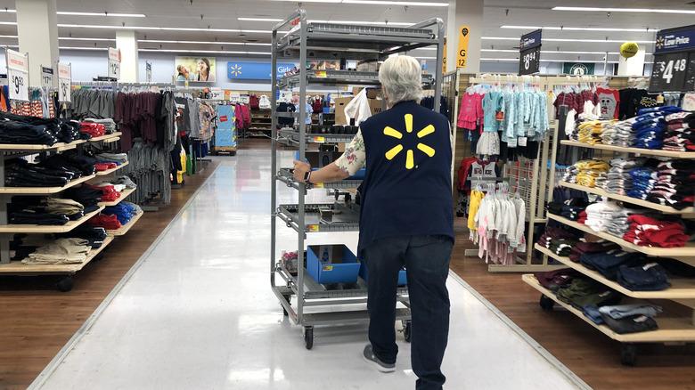 Walmart employee pushing cart through store