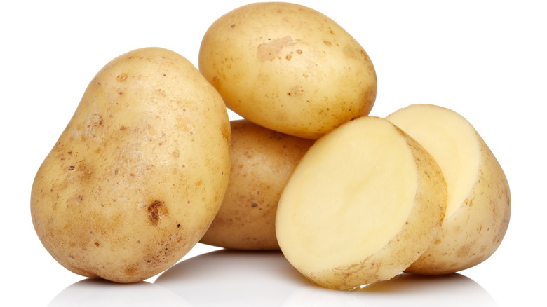 Whole and sliced potatoes on white background