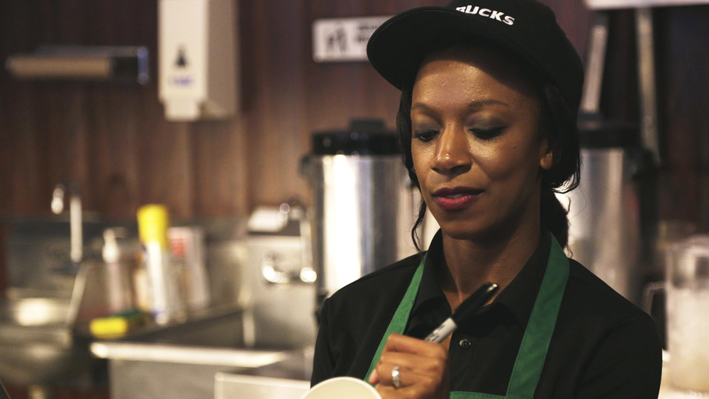 Starbucks worker writing on cup