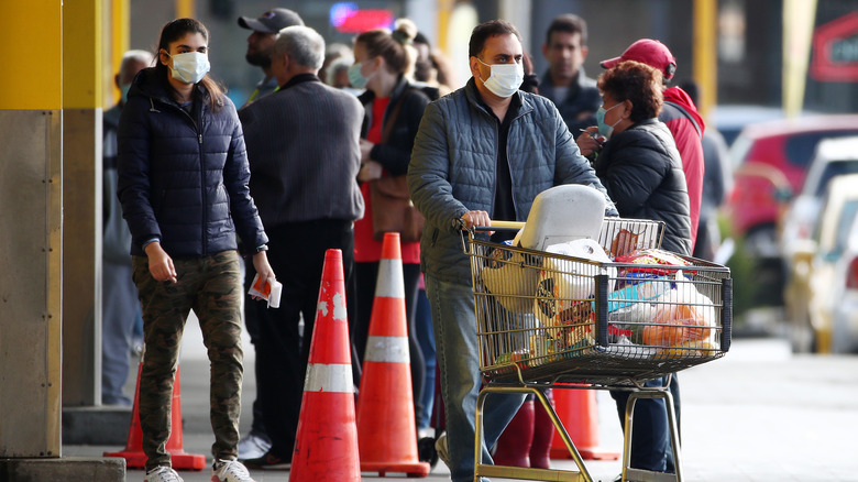 Shopper leaving grocery store with line of customers outside