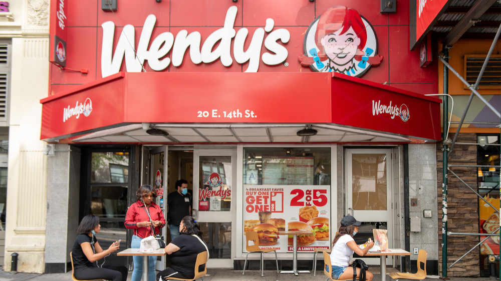 People eating outside of a Wendy's