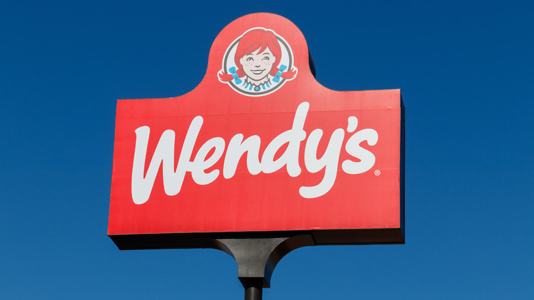 A Wendy's sign against a blue sky