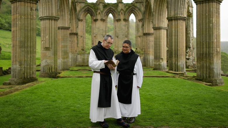 Two monks inside monastery ruins