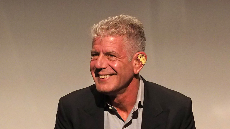 Anthony Bourdain with flower behind ear smiling