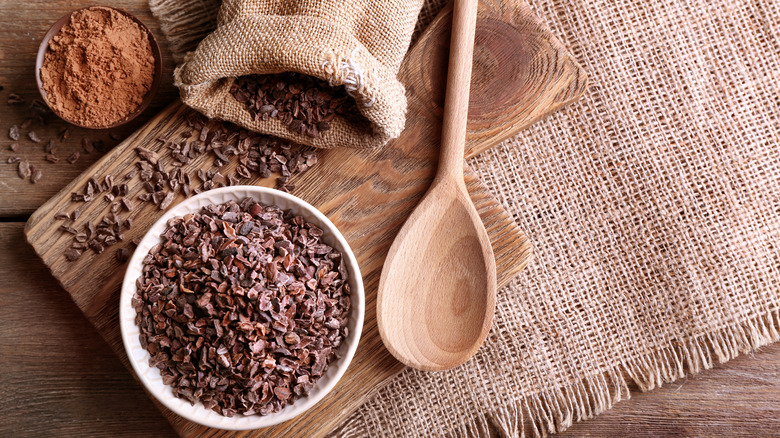 Cocoa nibs in bowl on wood table
