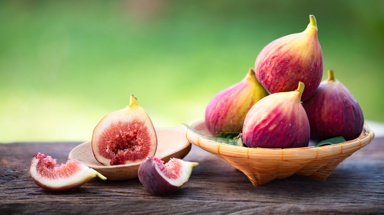 Ripe figs on wood table and in bowl
