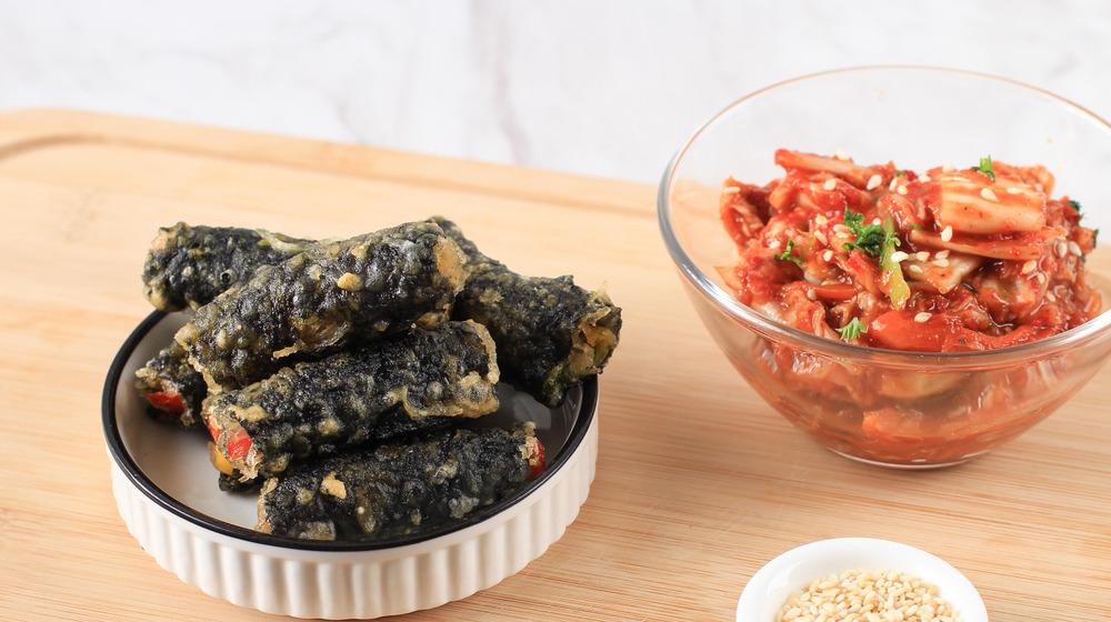 Gimmari in bowl next to kimchi