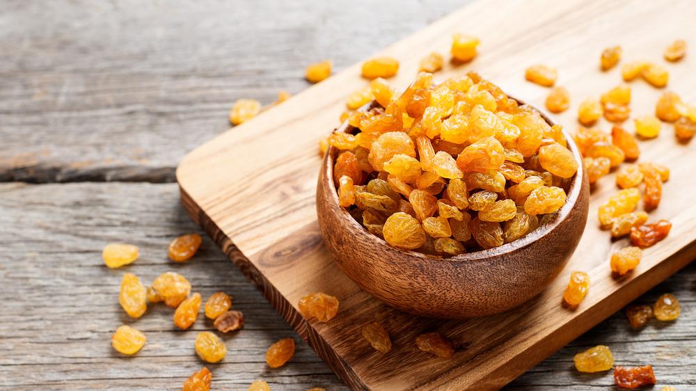 Golden raisins in a wooden bowl