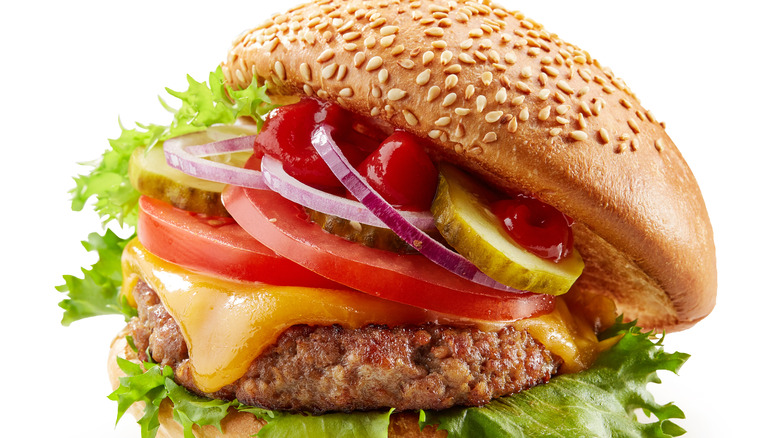 Burger with toppings inside sesame seed bun