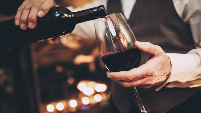 Waiter pouring glass of red wine