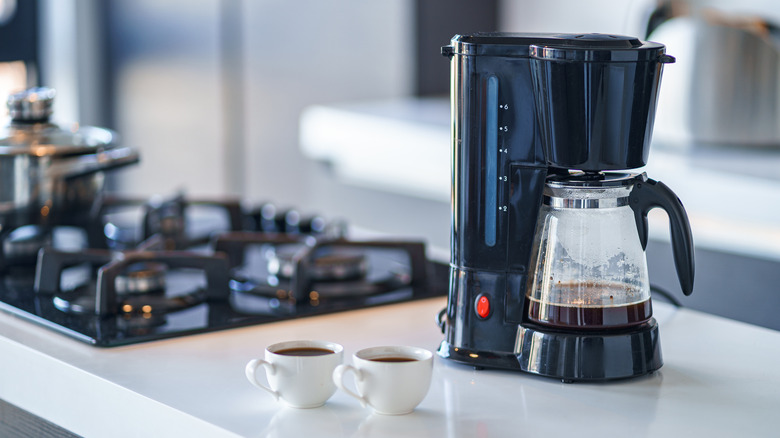 Drip coffee maker on counter with two cups of coffee