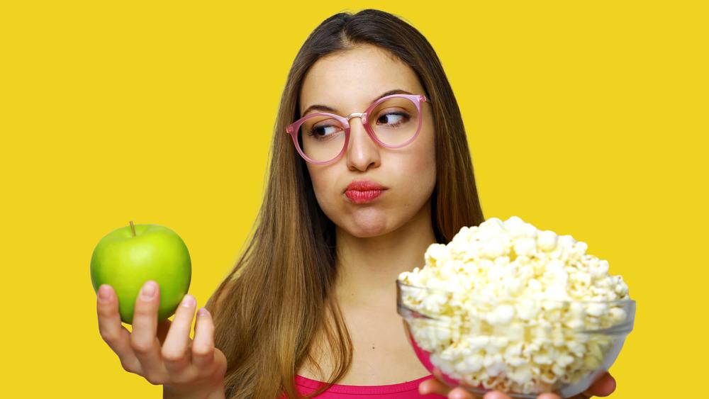 Woman choosing between apple and popcorn