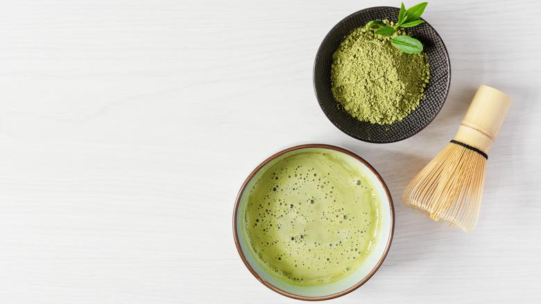 Cup of organic matcha tea with bowl of matcha powder