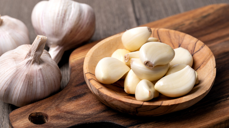 Peeled garlic cloves in a wooden dish on a wooden cutting board with unpeeled garlic heads in the background