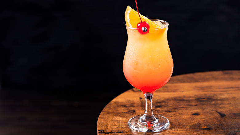 A hurricane cocktail sitting on a table.