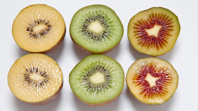 Three different colors of kiwis cut in half