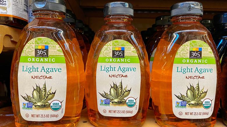 Three bottles of agave nectar on a shelf