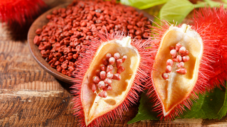 Annatto seeds in bowl and whole fruit