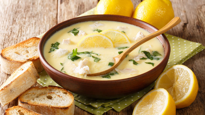 Bowl of avgolemono soup with lemon and bread