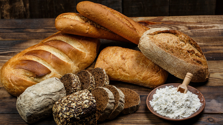 Loaves of bread and a bowl of bread flour on a table