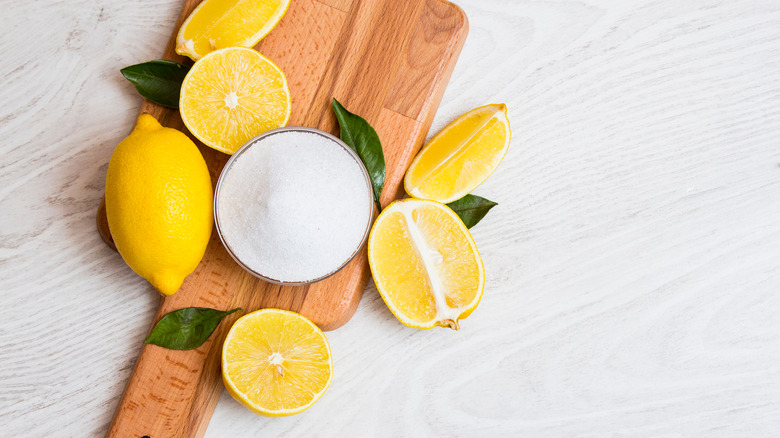 Citric acid powder surrounded by lemons on wooden board